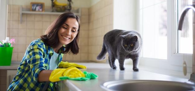 Mulher jovem e bonita feliz em luvas amarelas está limpando a cozinha com equipamento especial e brinca com um gato fofo