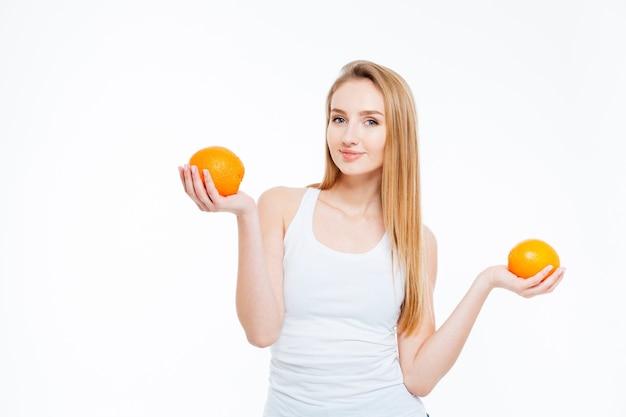 Mulher jovem e bonita feliz em pé e segurando duas laranjas sobre fundo branco