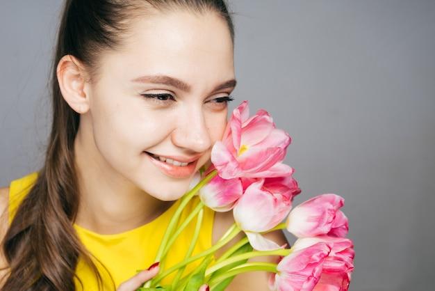 Mulher jovem e bonita feliz em um vestido amarelo se alegra na primavera e sorri segurando um buquê de flores cor de rosa