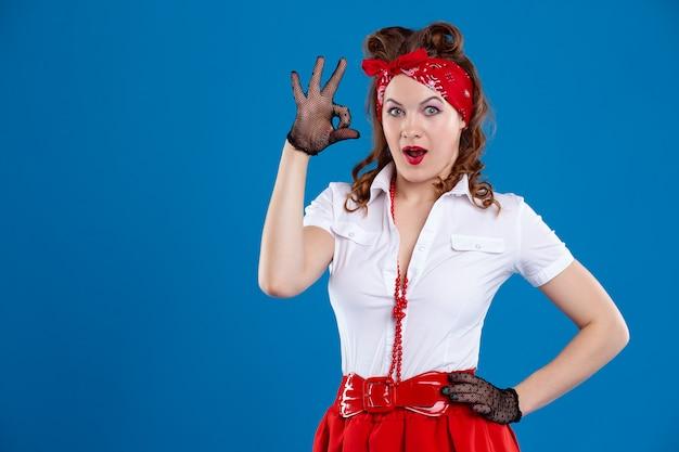 Mulher jovem e bonita feliz mostrando o sinal okey, vestida no estilo de pin-up. uma menina levanta no tiro retro do estúdio da forma e do conceito do vintage, em um fundo azul.