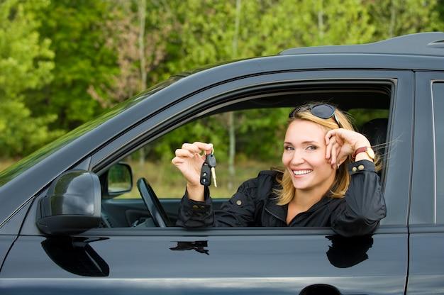 Mulher jovem e bonita feliz no novo carro com as chaves - ao ar livre