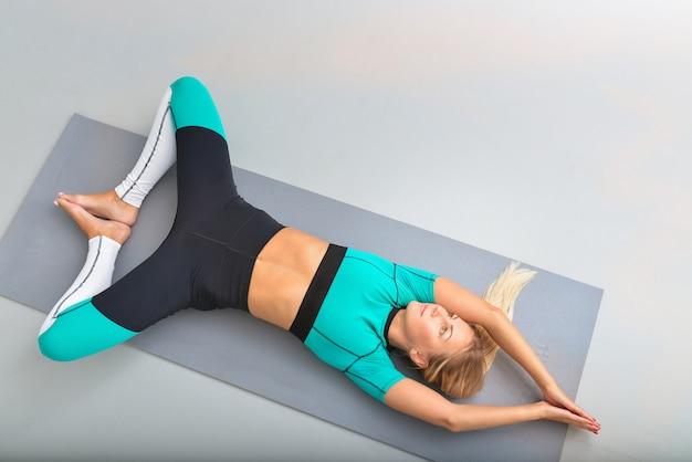 Mulher jovem e bonita feliz no sportswear colorido brilhante malhando dentro de casa, na esteira. menina deitada de costas no yoga relaxar pose. vista superior, conceito de fitness e estilo de vida.