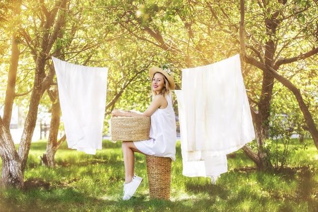 Mulher jovem e bonita feliz pendurando roupas limpas no jardim