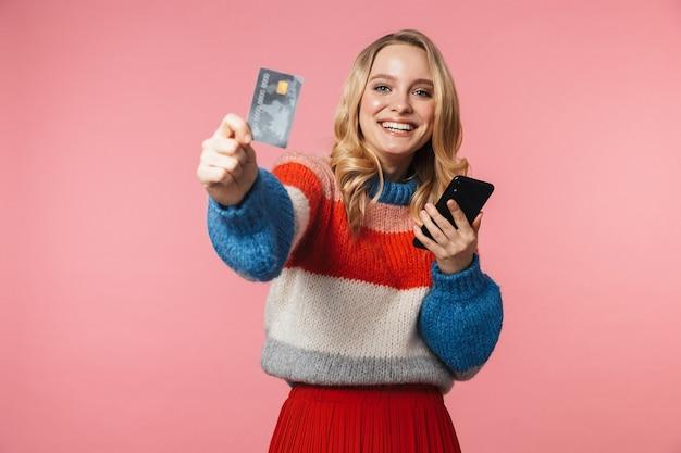 Mulher jovem e bonita feliz posando isolada sobre uma parede rosa, usando um telefone celular, segurando um cartão de crédito