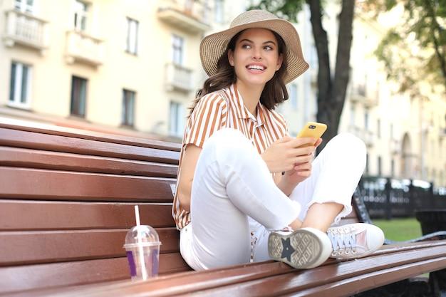 Mulher jovem e bonita feliz relaxando no banco do parque da cidade, segurando o celular nas mãos.