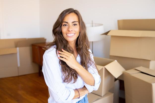 Mulher jovem e bonita feliz se mudando para um apartamento novo, em frente a uma pilha de caixas de papelão abertas, olhando para a câmera