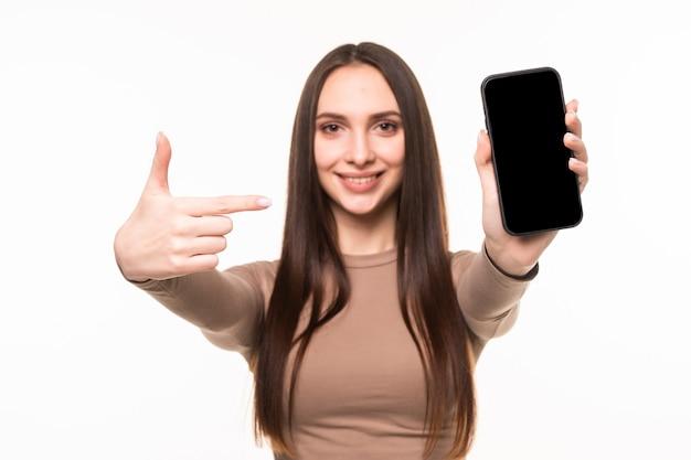 Mulher jovem e bonita feliz segurando uma tela em branco do celular e apontando o dedo sobre a parede branca