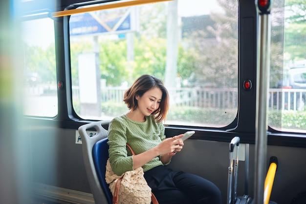 Mulher jovem e bonita feliz sentada no ônibus da cidade, olhando para o celular