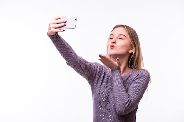 Mulher jovem e bonita feliz sonhando em uma camiseta listrada isolada na parede branca tirando uma selfie e dando um beijo no ar
