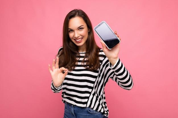Mulher jovem e bonita feliz sorridente, vestindo um suéter listrado isolado sobre um fundo com espaço de cópia, mostrando o gesto ok, olhando para a câmera, mostrando a tela do telefone móvel. mock up, cutout