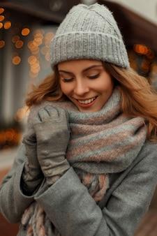 Mulher jovem e bonita feliz sorrindo em roupas de malha vintage com chapéu da moda e lenço estiloso nas férias perto das luzes