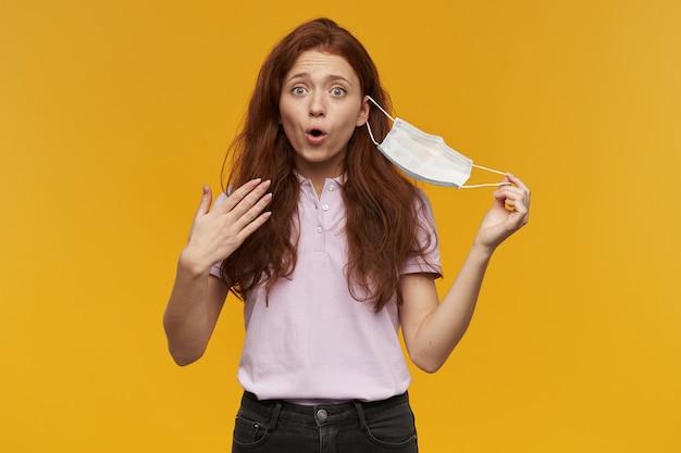 Mulher jovem e bonita feliz tirando a máscara protetora médica e respirando ar fresco na parede amarela