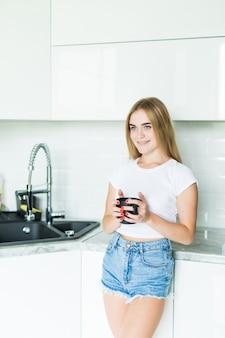 Mulher jovem e bonita feliz tomando café em casa de manhã