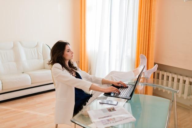 Mulher jovem e bonita feliz trabalhando e usando laptop, dentro de casa