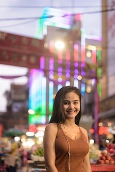 Mulher jovem e bonita feliz turista asiática sorrindo em chinatown à noite