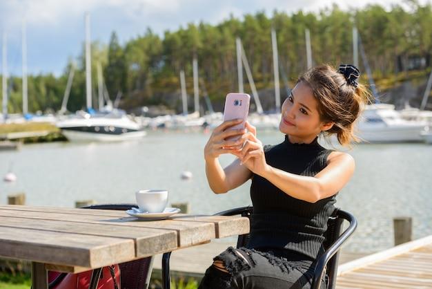 Mulher jovem e bonita feliz turista asiática tirando uma selfie no restaurante perto do cais