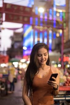 Mulher jovem e bonita feliz turista asiática usando o telefone em chinatown à noite