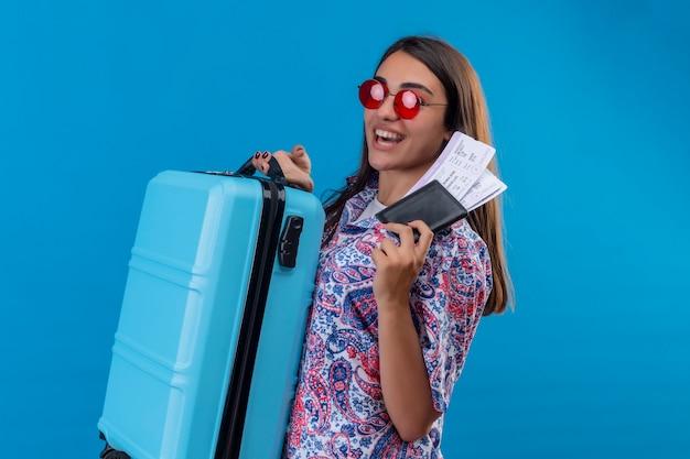 Mulher jovem e bonita feliz, usando óculos escuros vermelhos, segurando uma mala azul e bilhetes, sorrindo alegremente com uma cara feliz em pé sobre um fundo azul