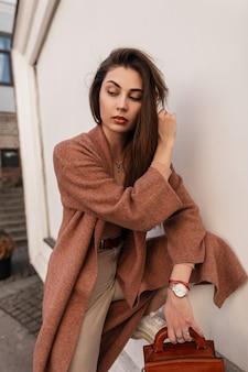 Mulher jovem e bonita feminina com um casaco elegante em calças bege elegantes com bolsa de couro marrom endireita o cabelo comprido perto de uma parede vintage na cidade. mulher atraente e elegante posando de modelo. estilo de primavera.