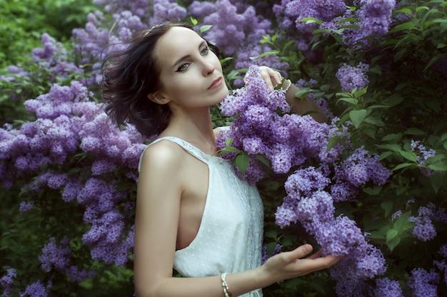 Mulher jovem e bonita fica entre os arbustos que florescem lilás no jardim.