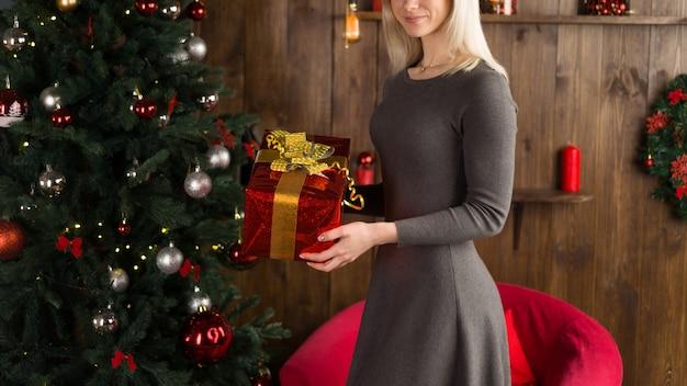 Mulher jovem e bonita fica perto de uma árvore de natal e tem uma caixa de presente nas mãos no interior da casa de ano novo. - imagem