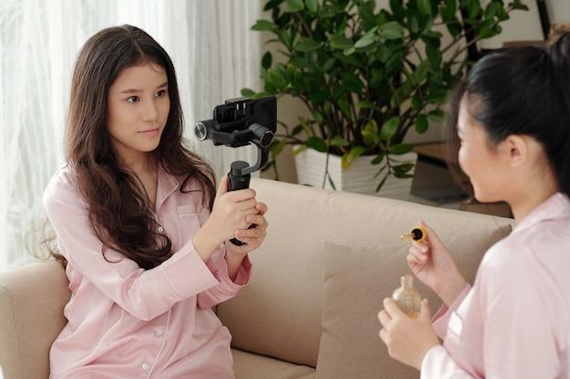 Mulher jovem e bonita filmando sua amiga, contando sobre sua rotina de cuidados com a pele e explicando como usar o f ...