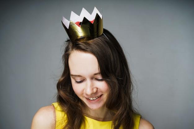 Mulher jovem e bonita fofa em um vestido amarelo sorrindo, na cabeça uma coroa de ouro