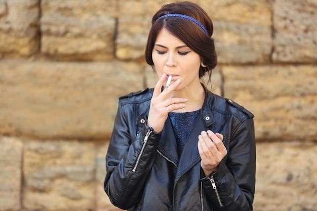 Mulher jovem e bonita fumando maconha ao ar livre