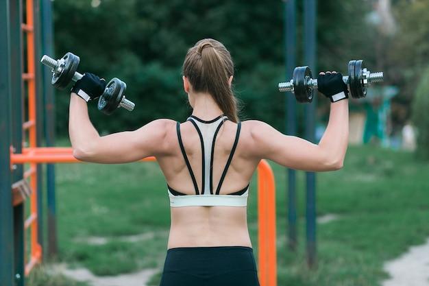 Mulher jovem e bonita funciona em seus braços, costas e ombros com halteres fora