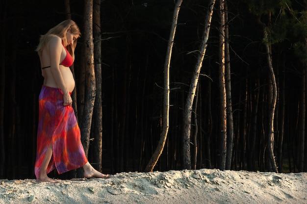 Mulher jovem e bonita grávida com uma barriga nua caminha na natureza perto da floresta e do lago.
