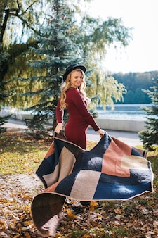 Mulher jovem e bonita grávida em um vestido vermelho e um chapéu elegante no parque outono.