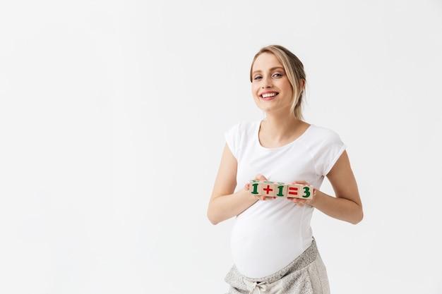 Mulher jovem e bonita grávida isolada sobre um fundo branco