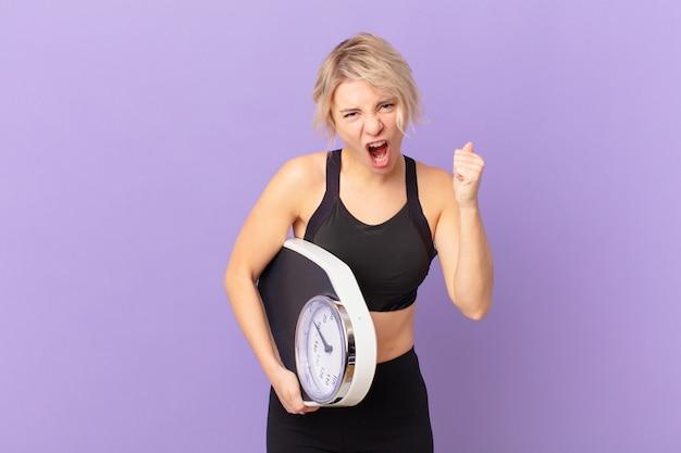 Mulher jovem e bonita gritando agressivamente com uma expressão de raiva. conceito de dieta