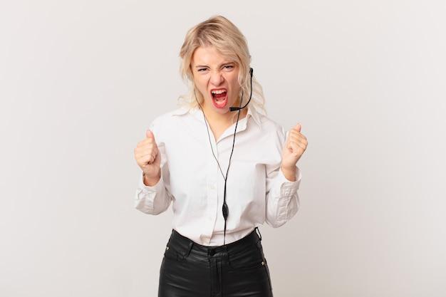 Mulher jovem e bonita gritando agressivamente com uma expressão de raiva. conceito de telemarketing