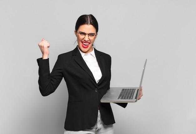 Mulher jovem e bonita gritando agressivamente com uma expressão de raiva ou com os punhos cerrados, celebrando o sucesso. conceito de laptop