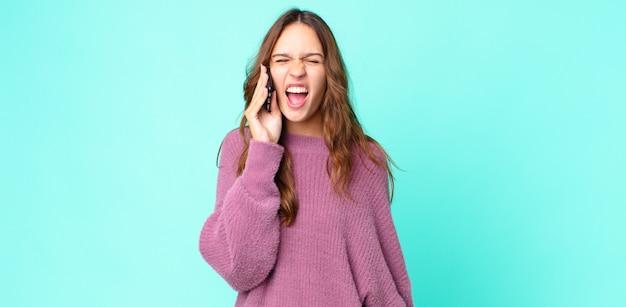 Mulher jovem e bonita gritando agressivamente, parecendo muito zangada e usando um smartphone