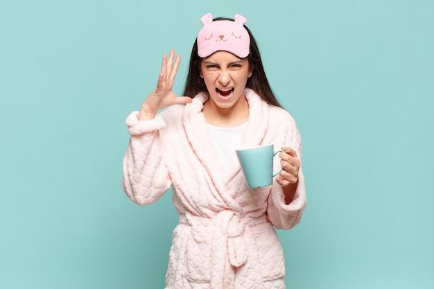 Mulher jovem e bonita gritando com as mãos no ar, sentindo-se furiosa, frustrada, estressada e chateada. acordar de pijama conceito