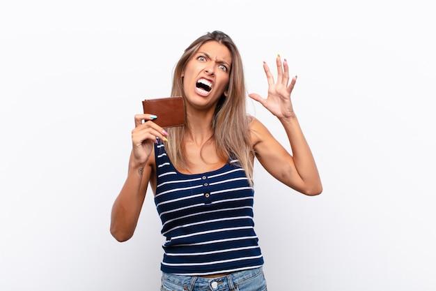 Mulher jovem e bonita gritando com as mãos no ar, sentindo-se furiosa, frustrada, estressada e chateada com uma carteira de couro.