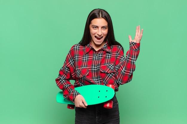 Mulher jovem e bonita gritando com as mãos no ar, sentindo-se furiosa, frustrada, estressada e chateada. conceito de skate