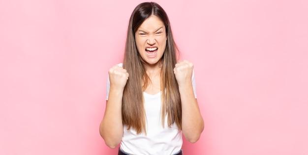 Mulher jovem e bonita gritando triunfantemente, rindo e se sentindo feliz e animada enquanto celebra o sucesso
