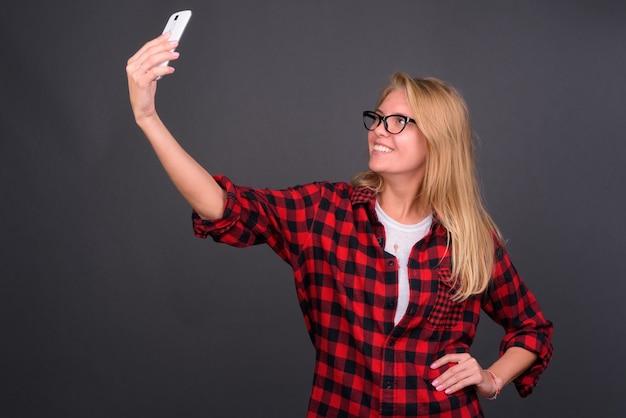 Mulher jovem e bonita hippie com cabelo loiro e óculos contra uma parede cinza