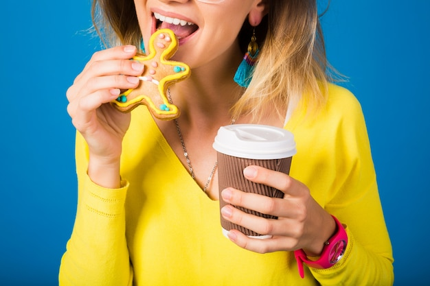 Mulher jovem e bonita hippie, comendo biscoitos, bebendo café