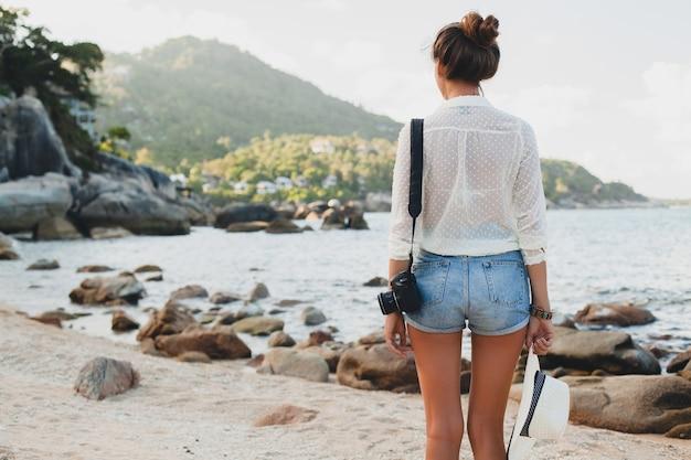 Mulher jovem e bonita hippie nas férias de verão na ásia, relaxando em uma praia tropical, câmera fotográfica digital, estilo boho casual, paisagem do mar, corpo magro bronzeado, viajar sozinho, liberdade