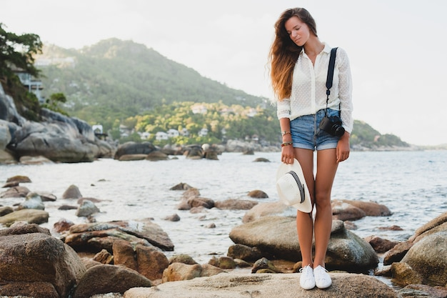 Mulher jovem e bonita hippie nas férias de verão na ásia, relaxando em uma praia tropical, câmera fotográfica digital, estilo boho casual, paisagem do mar, corpo magro bronzeado, viajar sozinho