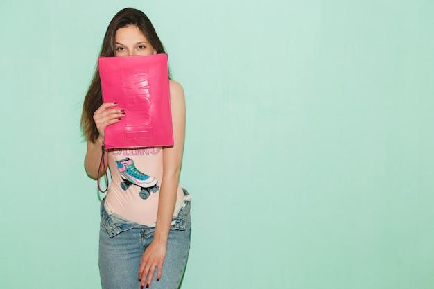 Mulher jovem e bonita hippie posando contra uma parede azul, segurando a bolsa rosa na moda