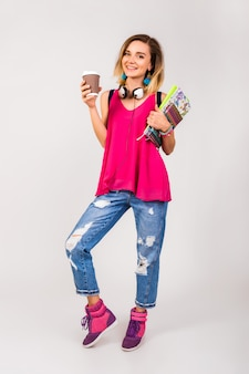 Mulher jovem e bonita hippie, sapatos rosa e top segurando livros e tomando café