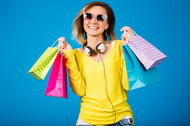 Mulher jovem e bonita hippie segurando sacolas de papel colorido