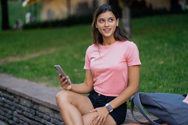 Mulher jovem e bonita hippie usando telefone inteligente na embalagem