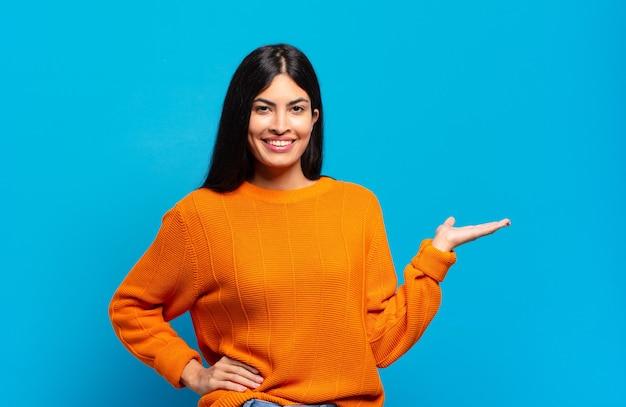 Mulher jovem e bonita hispânica sorrindo, sentindo-se confiante, bem-sucedida e feliz, mostrando o conceito ou ideia no espaço da cópia ao lado
