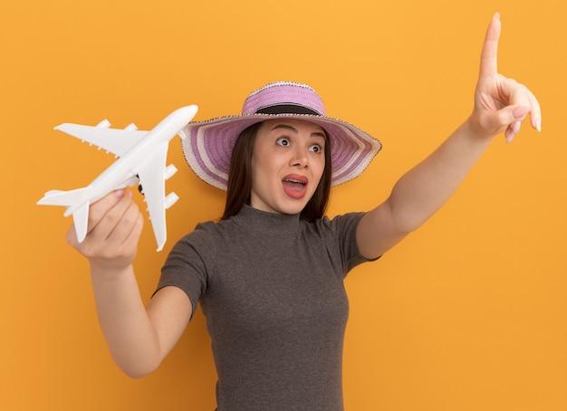 Mulher jovem e bonita impressionada com um chapéu segurando um brinquedo de avião